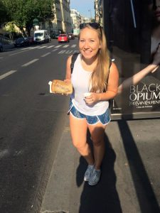 Woman holding crepe on street in Paris