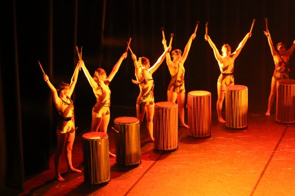 Students dancing on stage with drums