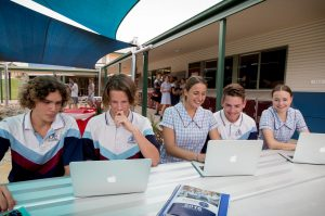 Students on laptops in outside area