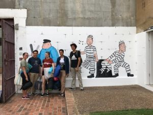 Students posing in front of jail themed graffti