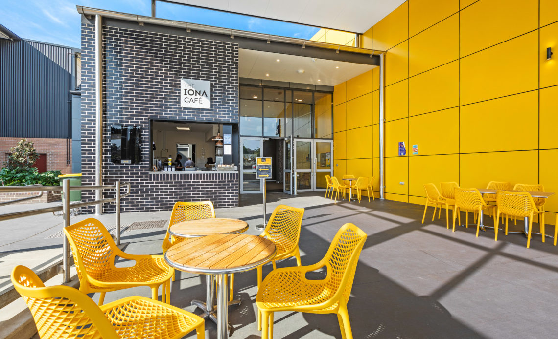 The exterior of a cafe with a bright yellow wall and yellow seats
