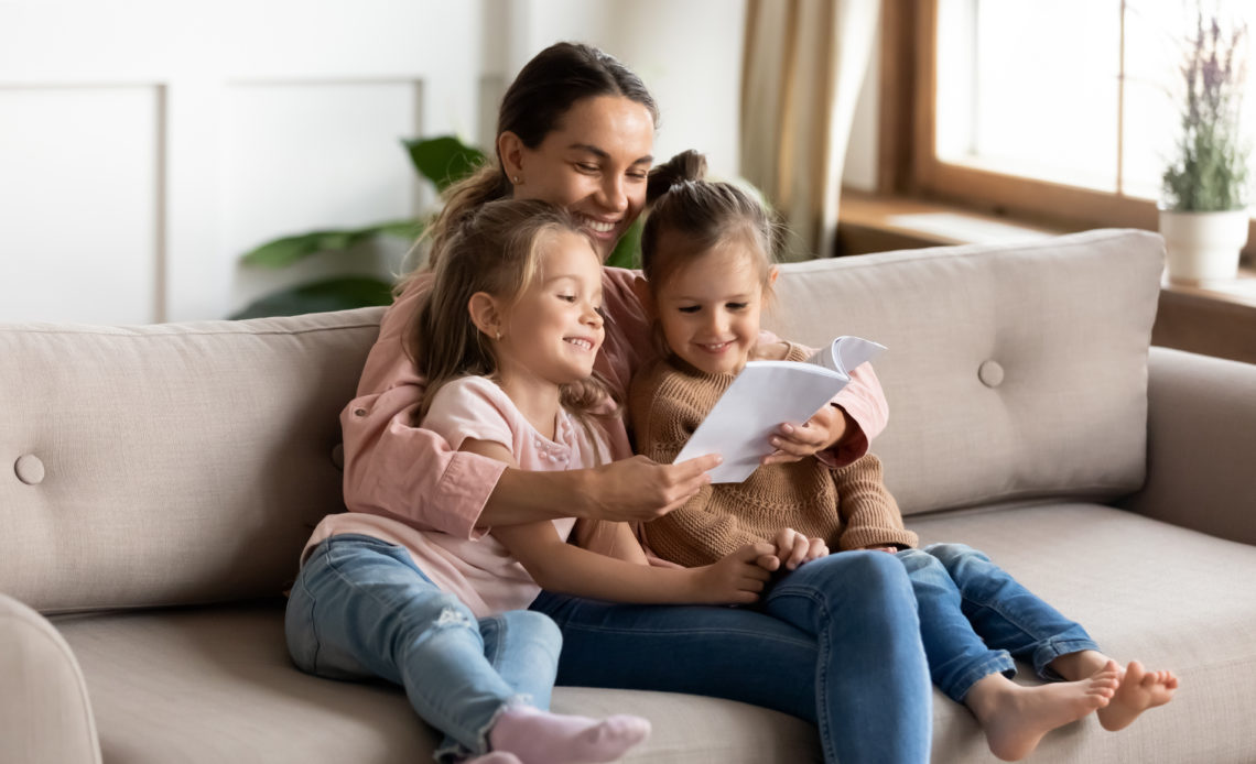 Happy family sit on sofa having fun together at home